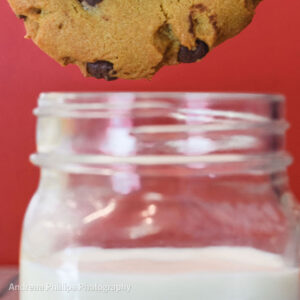 Chocolate chip cookie dunked in milk